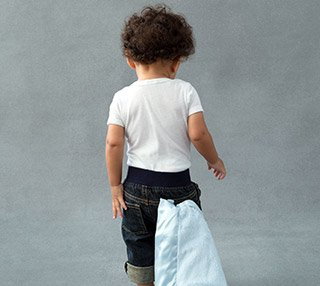 Backside view of toddler standing with his security blanket tucked in back pocket of his shorts