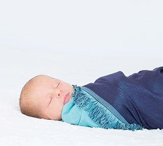 Side angled view of sleeping baby wrapped in swaddle blanket