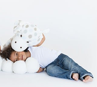 Front view of toddler laying on her side wrapped with her Little Giraffe baby toy