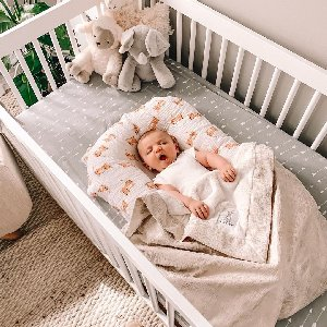 Baby yawns in our Lustre Rain Baby Blanket in cream.