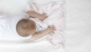 Baby laying on pink blanket