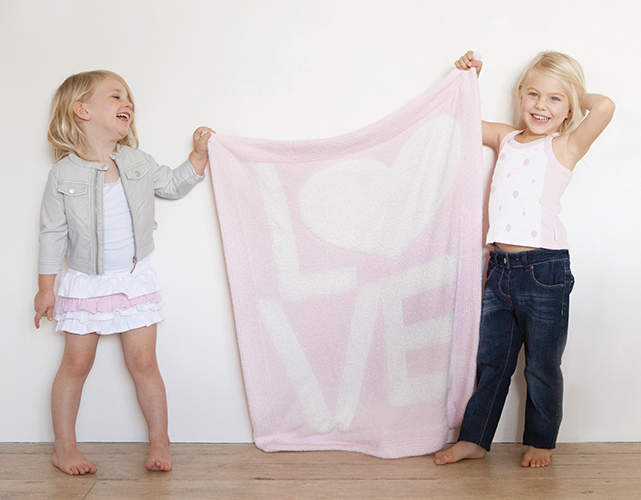 Two girls holding up a LOVE blanket